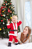 Young mother playing with baby dressed in Santa costume