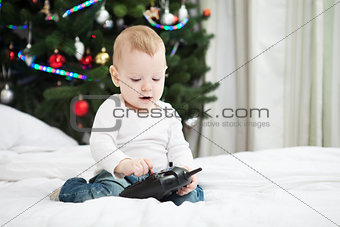 Toddler boy holding RC controller while sitting on bed at home at christmas time