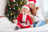 Happy mother putting Santa costume on toddler son at home