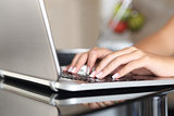 Woman hands working with a laptop at home