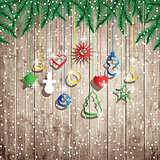 Fir tree branches and hanging toys on the wooden board background.