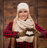 Woman in gloves show love sign