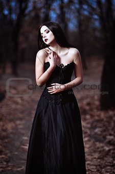 A beautiful sad goth girl stands in grove