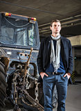 Fashion shot: handsome young man wearing jeans and coat against the tractor