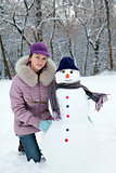 Beautiful girl near a snowman