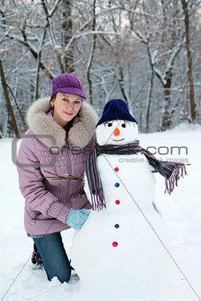 Beautiful girl near a snowman