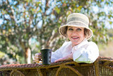 Smiling woman  with cup in the garden