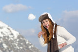 Playful woman throwing a snow ball in winter on holidays