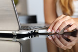 Woman hand plugging an usb  pendrive on a laptop at home