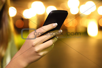 Close up of a woman hand using a smart phone in the night