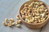 Bowl of cashews resting on wooden table
