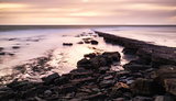 Beautiful toned seascape landscape of rocky shore at sunset