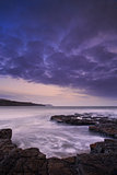 Beautiful toned seascape landscape of rocky shore at sunset