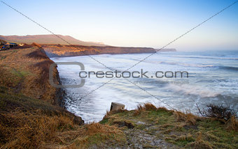 Beautiful coastal landscape at sunrise with cliffs and misty glow