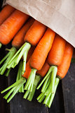 Fresh organic carrots in a paper bag