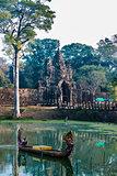 woman boat moat south gate bridge Angkor Thom Cambodia