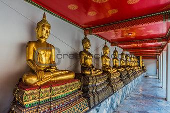 aligned golden buddha statues Wat Pho temple bangkok Thailand