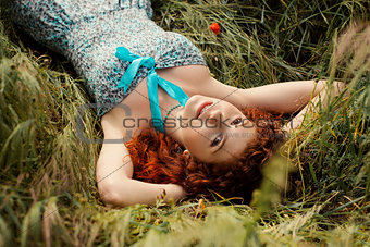 Beautiful redhead woman lying on grass