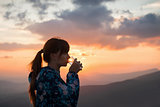 Woman drinking water on sunset background