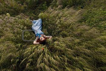 Beautiful woman sleeping on tall grass