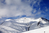 View on off-piste snowy slope in wind day