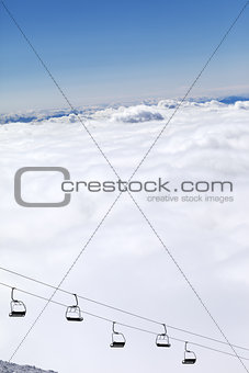 Chair-lift and mountains under clouds in sun day