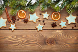 Christmas wooden background with fir tree, spices, gingerbread cookies