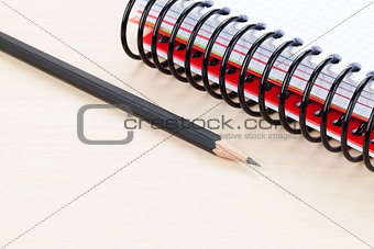Office table with blank notepad and pencil