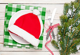 Santa hat on plate, silverware and christmas tree