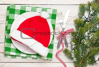 Santa hat on plate, silverware and christmas tree
