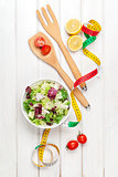 Fresh healthy salad, utensils and tape measure