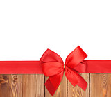 Red ribbon with bow over wood background