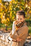 Portrait of happy young woman in autumn park hiding behind scarf