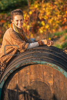 Portrait of smiling young woman near wooden barrel in autumn out