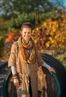 Portrait of smiling young woman standing near wooden barrel in a