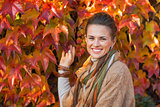 Portrait of happy young woman in front of autumn foliage