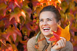 Portrait of smiling young woman with autumn leafs in front of fo
