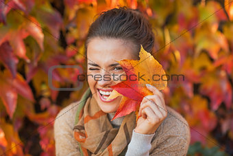 Portrait of happy young woman hiding behind autumn leafs in fron