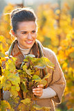 Portrait of happy young woman standing in autumn vineyard