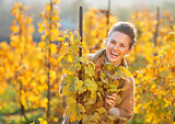 Portrait of happy young woman in autumn vineyard looking out fro