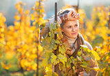 Portrait of thoughtful young woman standing in autumn vineyard