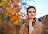Portrait of thoughtful young woman standing in autumn outdoors i