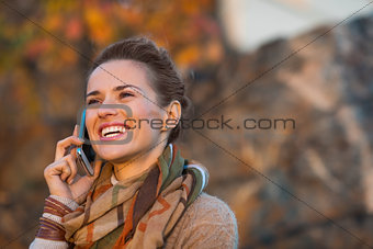 Portrait of happy young woman in autumn evening outdoors talking