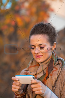Portrait of young woman in autumn evening outdoors writing sms