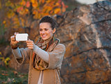 Happy young woman in autumn evening outdoors taking photo with c