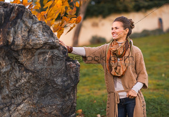 Portrait of happy young woman standing in autumn park in evening