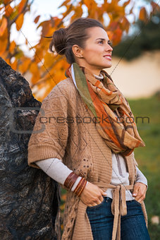 Portrait of young woman in autumn outdoors in evening
