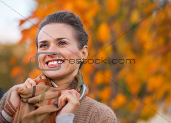 Portrait of happy young woman in autumn outdoors in evening