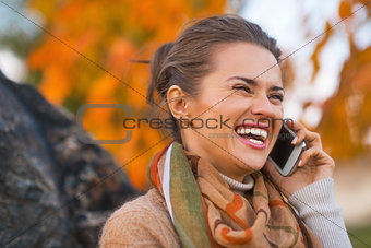 Portrait of happy young woman in autumn outdoors in evening talk