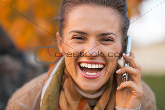 Portrait of smiling young woman in autumn outdoors in evening ta